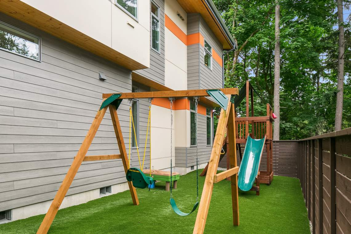 Fully fenced yard with artificial grass and play area