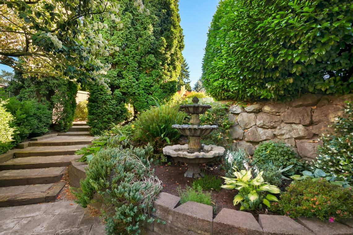 Mature landscaping, natural stone hardscaping, and Italian fountain